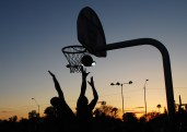 Players reach for the ball at sunset during a pick-up basketball game at Encanto Park in Phoenix, Arizona on Februrary 26, 2017.