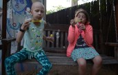 Harmony and Cali blow bubbles in the family's backyard.