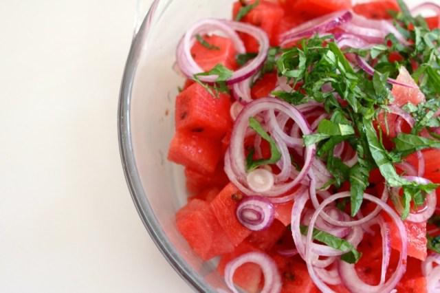 Watermeloen mengen met rode ui en munt