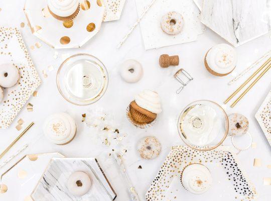 feestelijke tafel met witte donuts en gouden elementen