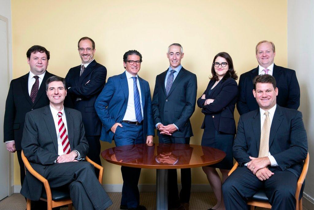 A group of attorneys around a table with slight smiles in business suits -NYC professional malpractice defense