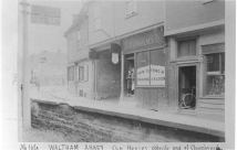 Photograph of shops on the south side of Church Street No.2 showing a barber (E.Lawrence) and a barber's pole the lather boys (wages 2s. per week) were Master Bayford (right) and Roe (left) No.3 a sports shop also showing costume.