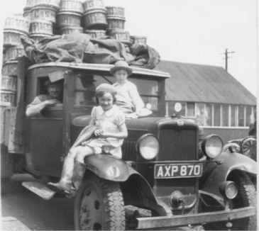 Mr Evans in driving seat and children on bonnet of lorry loaded with baskets of tomatoes and cucumbers ready to leave Breach Barns Nursery Waltham Abbey for covent garden market