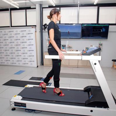 Un sujeto instrumentalizado con sistema de análisis de movimiento realiza un ensayo para estudiar el movimiento, la pisada y las presiones del pie con un modelo de calzado de tacón sobre un tapiz sensorizado, en el marco del proyecto Taconshoe.