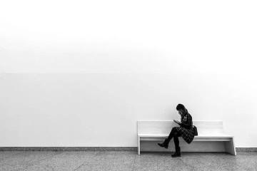 Mujer sentada en un banco; fotografía minimalista