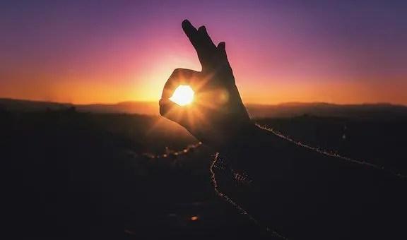 Mano señalando el sol despidiéndose