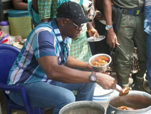 Ekiti Governor, Ayodele Fayose dishes food in a food stall