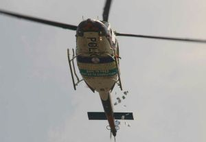 Change is Here! Police in helicopter share flyers on security sensitization.