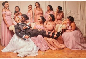 Bride Carries Groom On Her Laps, Bridesmaids Hold His Legs For Her To Kiss Him (Photo)