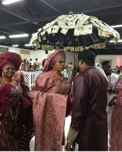 LOL!! Nigerian Woman Wrapped Her Umbrella With Dollars Cash To An Event (photo)