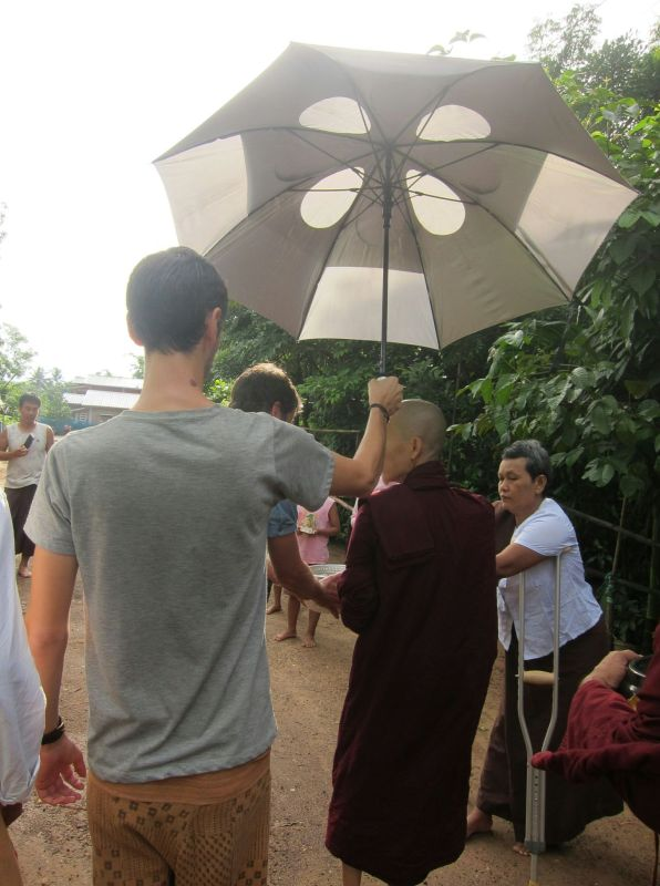 "Some people were obsessed with pleasing Sayadaw, being the celebrity that he was. Somebody thrust an umbrella in my hand and said, ""Hold it for Sayadaw for the rain and for the sun."" It was sunny, so in this photo you can see me holding the auspicious umbrella of ultraviolet protection. Soon after I raised it, Sayadaw turned to me, stopping the monk line, and calmly said, ""I don't need for sun. Just for rain,"" and my job was over."