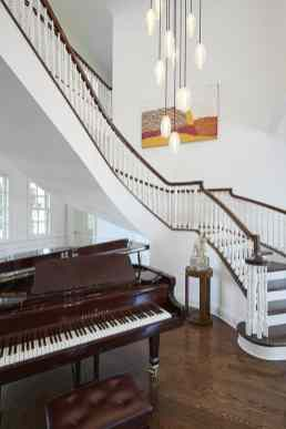 grand piano in a stairwell foyer of a remodel project featuring a unique brass ring chandelier as shown in modern reduction in california home magazine