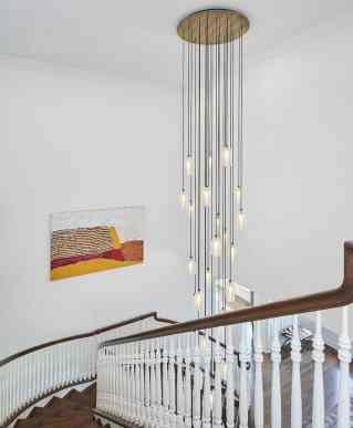 dramatic chandelier in stairwell foyer of a remodel project featuring a unique brass ring chandelier as shown in modern reduction in california home magazine
