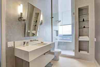tone-on-tone white bathroom vanity with tilted mirror and corner glass-front cabinet with designs by eggersmann and schmalenbach