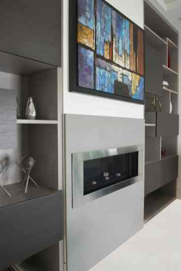 ultra contemporary fireplace in storage and art display wall designed and installed by eggersmann
