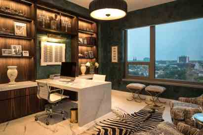 warm wood cases in a library wall set off by a modern stone waterfall top desk with ample room for entertaining to enjoy the city view