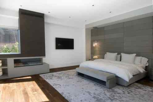 modern master bedroom with fireplace surround and niches designed by eggersmann