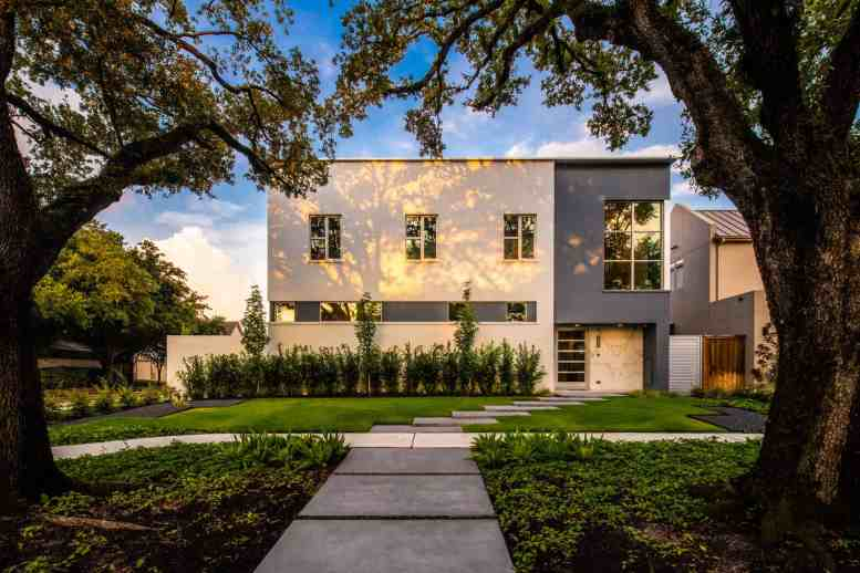 new construction home in upper kirby area of houston features ultra modern architecture framed by beautiful century old oak trees