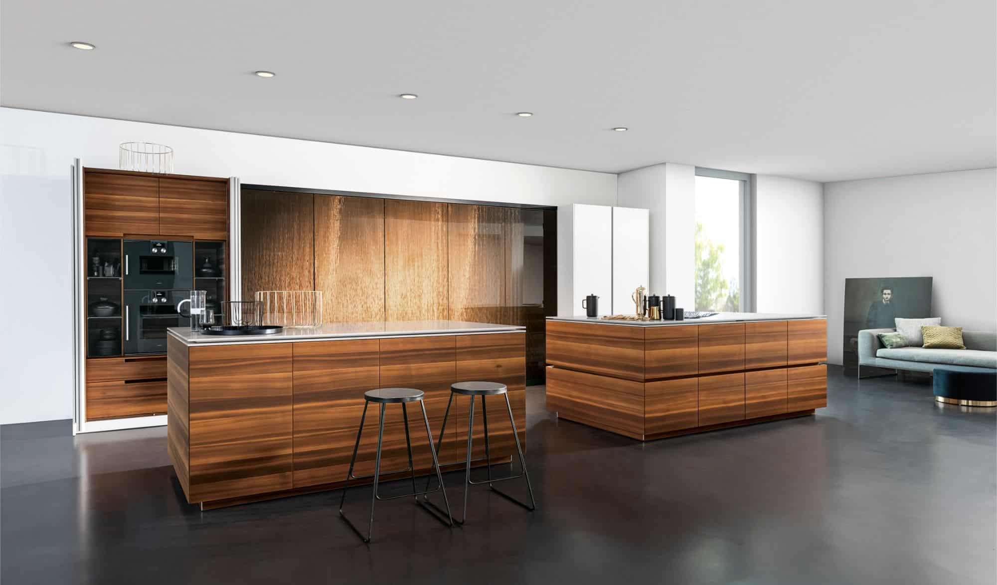 eggersmann larch wood veneer islands featuring moving worktops from the motion collection with with the works tall cabinets with interlink bronze finish