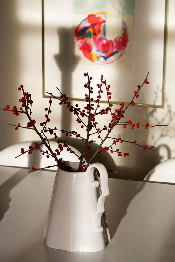 Stems of red berries in a white jug