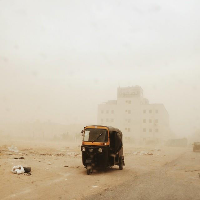 A tuk-tuk riding through the haze o a sandstorm in October 6 City. Photo by Owise Abuzaid
