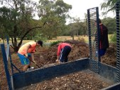 Shows mulch being shovelled into trailer, Edward Hunter Heritage Bush Reserve