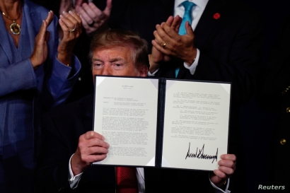 FILE - U.S. President Donald Trump holds an executive order relieving qualified disabled veterans of federally held student loan debt at the AMVETS (American Veterans) National Convention in Louisville, Kentucky, Aug. 21, 2019.