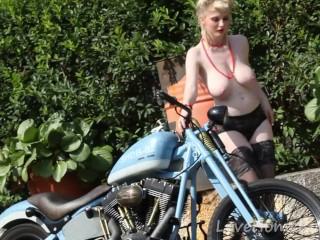 Cute blonde enjoys posing next to a bike