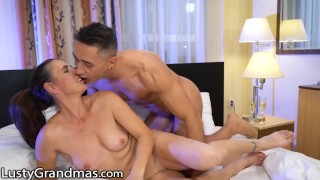 LustyGrandmas GILF Greets Stud in His Bedroom in White Lingerie