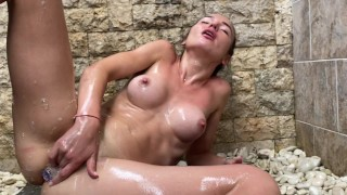 Horny bitch is playing in the shower with her wet pussy and anal plug in her asshole