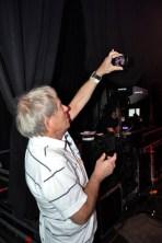 Bandchef Klaus Flieger hält am Bühnenzugang per Handykamera fest, was seine Truppe auf der Bühne zaubert. (Foto: Reiner Züll)