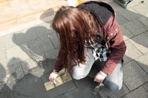 Nach der Verlegung der Stolpersteine wischte eine Schülerin die Gedenktafeln sauber. Bild: Michael Thalken/Eifeler Presse Agentur/epa