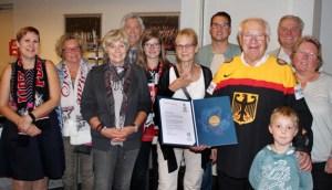 Für seinen zweijährigen Einsatz als WM-Botschafter verlieh der Eishockey-Weltverband dem Ehrenamtler Dieter Züll eine Dankesurkunde und eine Goldmedaille, die er Eifeler Eishockey-Fans und Freunden nach der Scheckübergabe in der Lanxess-Arena präsentierte. Foto: Züll