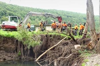 Forstwirte aus der Nationalparkverwaltung und Nachbarforstämtern unterstützen den Wasserverband bei Aufräumarbeiten an der Urft. Hier vor einem tiefen Einbruch in das Urftufer. Foto: Nationalparkverwaltung Eifel/A. Simantke