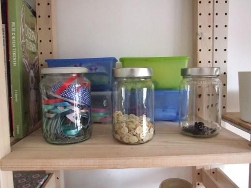 Potjes met knopen en lintjes en bakjes met diverse materialen.