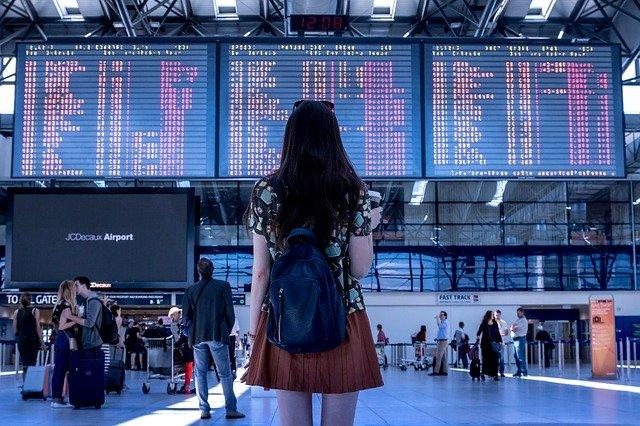 1人の女性が空港の出発ターミナルの大きなデジタル出発時刻表を見ている。一人での国際旅行に行く感じ - 函館英会話教室EigoLa