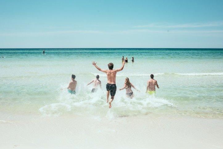 5人の友達がビーチから海に走って入る、海外旅行な雰囲気 - 函館英会話教室EigoLa