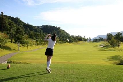 ゴルフをする女性の後ろ姿