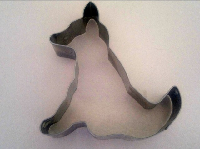 Cookie cutter in the shape of a dog. The dog is seated.