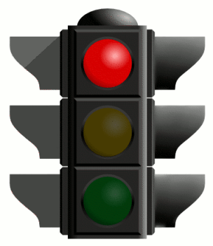 A traffic light with three colored bulbs: red, yellow, and green. The red light is lit up.