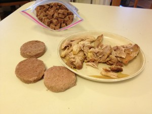 Chunks of dark meat chicken on a plate, round disks of dog food roll, a ziplock bag with pieces of dog food roll