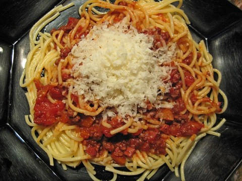 A plate of spaghetti with a red colored meat sauce and a pile of grated cheese on top