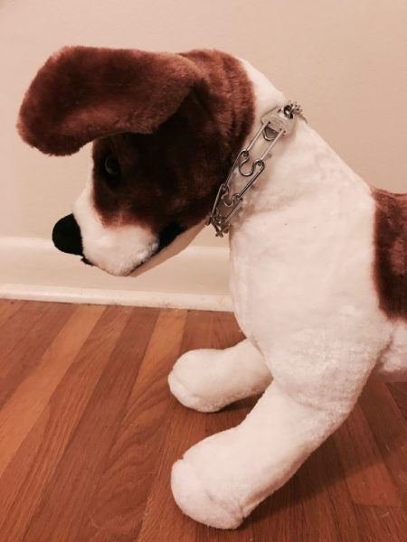 stuffed dog modeling a tightly fitted prong collar