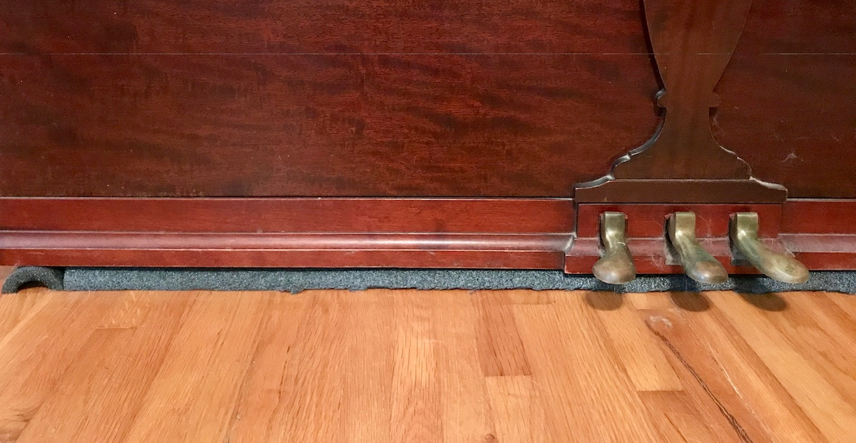 piano with foam pipe insulation running under the edge and under the pedals