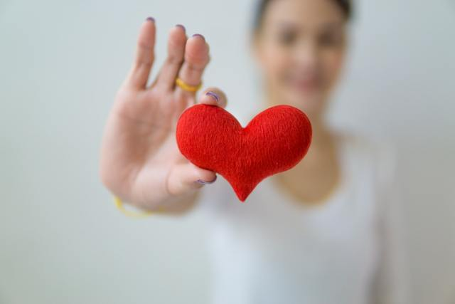 Blurred woman holding felt heart out into focus.