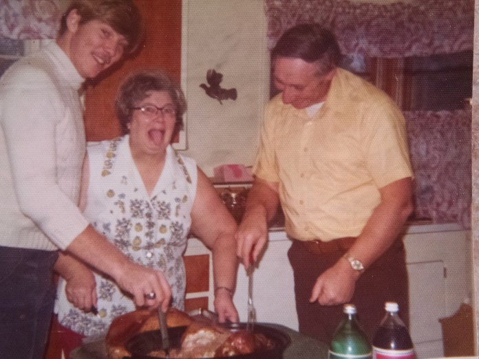 "Mom handled stress by going nuts, as evidenced by the carving of this Thanksgiving turkey. Based on my older brother Tom's mustache, this is sometime in the mid-'70s. Based on Dad's grin, he enjoyed it when Mom went nuts. At every feast, Mom would inquire, ""How's the turkey?"" I loved to jump in first: ""I've had worse,"" and Sue would add, ""It's a little dry."" Mom would go ballistic: ""But I watched it so close,"" never realizing we were pulling her leg and breaking her wishbone."