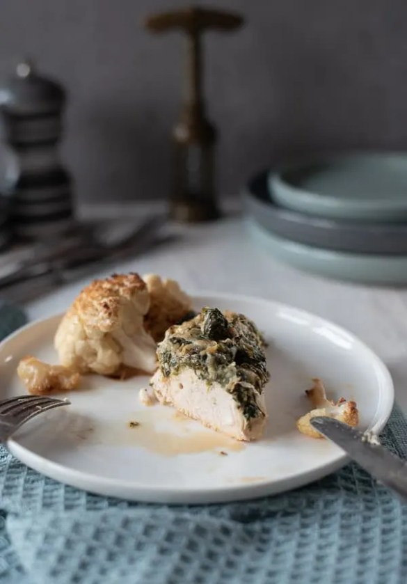 angeschnitte Hähnchenbrust mit Spinat-Käse-Haube auf einem weißen Teller