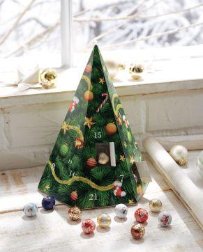 Adventskalender in Pyramidenform, gefüllt mit 24 Stück (110 g) Mini-Schokoladenkügelchen der Fa. Lindt & Sprüngli in 5 verschiedenen Geschmacksrichtungen. Alpenvollmilch-Schokolade (Kakao: 30% mindestens), Maße: ca. H26 x B16,5 cm, Gewicht: ca. 0,3 kg. Zutaten: Zucker, Kakaobutter, VOLLMILCHPULVER, Kakaomasse, MILCHZUCKER, MAGERMILCHPULVER, Emulgator: SOJALECITHIN, GERSTENMALZEXTRAKT, BUTTERREINFETT, Aroma. Allergiehinweis: Kann Spuren von Haselnüssen und Mandeln enthalten<br>