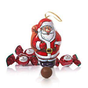 Dose in Weihnachtsmann-Form mit Aufhänger. Aus Metall gefertigt, gefüllt mit 75g Vollmilchschokoladenkugeln (Kakao 30% mind.) mit Milchcremefüllung (35%), Maße: ca. 12,5 x 6 x 8,2 cm, ca. 130 g. Zutaten: Zucker, VOLLMILCHPULVER, pflanzl. Fett (Ölpalme, Kokos), Kakaobutter, Kakaomasse, MAGERMILCHPULVER, MILCHZUCKER, Emulgator: SOJALECITHINE, natürliches Aroma. Nährwertangaben: Energie 2348 kJ (563 kcal); Fett 36g, davon gesättigte Fettsäuren 23g; Kohlenhydrate 54g, davon Zucker 54g; Eiweiß 5,8g; Salz 0,19g. Allergiehinweis: Kann Spuren von Erdnüssen, Schalenfrüchten und Gluten enthalten.<br>