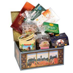 Geschenk-Set mit ingesamt 8 verschiedenen Leckereien. 1 Dose Elisen-Lebkuchen sortiert 300 g, 1 Packg. Elisen-Lebkuchen schokoliert 175 g, 1 Packg. Elisen-Lebkuchen glasiert 175 g, 1 Btl. Elisen-Lebkuchen schokoliert 250 g, 1 Btl. Elisen-Lebkuchen sortiert 250 g, 1 Packg. Vanille Kipferl 100 g, 1 Packg. Baumkuchenspitzen mit Rum 125 g, 1 Packg. Nuss-Sterne 125 g, Maße: ca. 31,7 x 24,5 x 15 cm, Gewicht: ca. Inhalt Netto 1,5 kg. Zutaten: Historische Runddose, Feinste Nürnberger Oblaten-Lebkuchen glasiert und schokoliert, bei schokolierten Lebkuchen 10% Schokolade: Ölsamen 25% (HASELNÜSSE, WALNÜSSE, MANDELN), Zucker, Orangeat (Orangenschalen, Glukose-Fruktose-Sirup, Zucker), WEIZENMEHL, Ma. Nährwertangaben: Baumkuchenspitzen mit Rum: Energie 1960 kJ (471 kcal); Fett 29,2g, davon gesättigte Fettsäuren 18g; Kohlenhydrate 40,9g, davon Zucker 32,4g; Eiweiß 5,8g; Salz 0,31g. Elisen-Lebkuchen: Energie 1944 kJ (972 kcal); Fett 23,3g, davon gesättigte Fettsäuren 6g; kohlenhydrate 53,1g, davon Zucker 35,3g; Eiweiß 9,8g; Salz 0,18g. Vanille Kipferl: Energie 2157 kJ (516 kcal); Fett 26,9g, davon gesättigte Fettsäuren 13,5g; Kohlenhydrate 61,7g, davon Zucker 20,6g; Eiweiß 6,2g; Salz 0,17g. Nuss-Sterne: Energie 1898 kJ (453 kcal); Fett 20,5g, davon gesättigte Fettsäuren 1,9g; Kohlenhydrate 56,3g, davon Zucker 47,7g; Eiweiß 8,5g; Salz 0,1g.. Allergiehinweis: Feinste Nürnberger Oblaten-Lebkuchen glasiert und schokoliert, bei schokolierten Lebkuchen 10% Schokolade: KANN SPUREN VON ERDNÜSSEN UND MILCH ENTHALTEN. Elisen-Lebkuchen 98mm, sortiert: KANN SPUREN VON ERDNÜSSEN UND MILCH ENTHALTEN Elisen-Lebkuchen 98mm,<br>